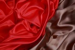Brown y el paño de seda rojo del satén de dobleces ondulados texturizan el fondo Fotografía de archivo libre de regalías