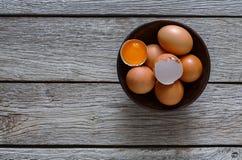 Brown y huevos orgánicos blancos en cuenco en el fondo de madera Foto de archivo