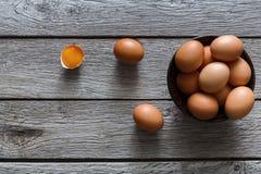 Brown y huevos orgánicos blancos en cuenco en el fondo de madera Fotografía de archivo