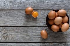 Brown y huevos orgánicos blancos en cuenco en el fondo de madera Imagen de archivo