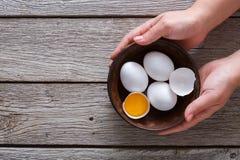 Brown y huevos orgánicos blancos en cuenco en el fondo de madera Fotografía de archivo libre de regalías