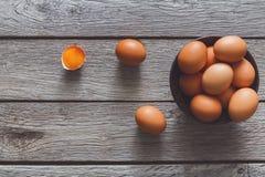 Brown y huevos orgánicos blancos en el fondo de madera Imagen de archivo libre de regalías