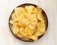 Brown yellow chips from natural potato in brown ceramic plate on white wooden background, top view, close-up. Brown yellow chips from natural potato in brown royalty free stock image