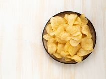 Brown yellow chips from natural potato in brown ceramic plate on white wooden background, top view, close-up, copy space. Brown yellow chips from natural potato royalty free stock photography
