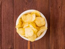 Brown yellow chips from natural potato in a white Cup on a brown. Wooden background, top view, close-up royalty free stock images