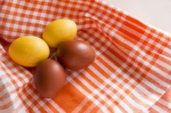 2 brown and 2 yellow Easter eggs on a towel in an orange cage, 4 boiled eggs stock photo