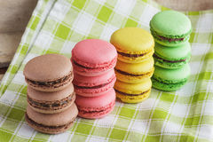 Brown, yellow, green and pink macarons on the plaid napkin. Brown, yellow, green and pink macarons on the green plaid napkin, soft focus background Royalty Free Stock Photography