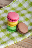 Brown, yellow, green and pink macarons on the plaid napkin. Brown, yellow, green and pink macarons on the green plaid napkin, soft focus background Stock Image