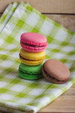 Brown, yellow, green and pink macarons on the plaid napkin. Brown, yellow, green and pink macarons on the green plaid napkin, soft focus background Stock Photo