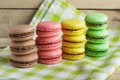 Brown, yellow, green and pink macarons on the plaid napkin. Brown, yellow, green and pink macarons on the green plaid napkin, soft focus background Stock Photography
