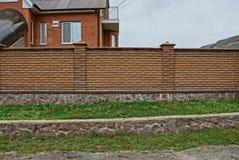 Brown-Zaun des Ziegelsteines und des Steins im grünen Gras auf der Straße Lizenzfreies Stockfoto