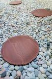 Brown-Ziegelstein auf weißem Stein im Garten Lizenzfreies Stockbild