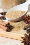 Brown-Zucker im hölzernen Löffel mit aromatischen Gewürzen Stockfotografie