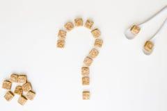 Brown-Zuckerwürfel formten als Fragezeichen auf weißem Hintergrund Beschneidungspfad eingeschlossen Unhealty süßes Suchtkonzept d Stockfotografie