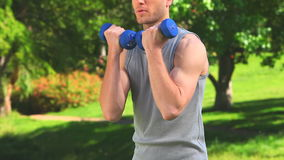 Brownhaired man using dumbbells Royalty Free Stock Photo