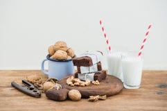 Brownie σοκολάτας φέτες που τυλίγονται στο έγγραφο και που κουράζονται με το σχοινί, γυαλιά γάλακτος, άχυρα λωρίδων, κούπα σμάλτω Στοκ Φωτογραφίες