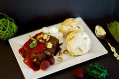 'brownie' avec la glace et les framboises Photographie stock libre de droits