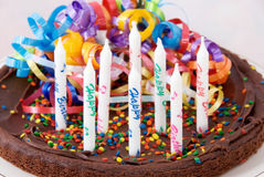Brownie Birthday Cake. With eight unlit candles that say Happy Birthday on them. Selective focus on the front candles Stock Image