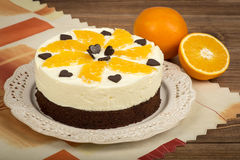Brownie cake with cream and oranges on the brown wooden background. Brownie cake with cream, oranges and chocolat on the  brown wooden background Stock Images