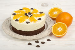 Brownie cake with cream and oranges on the white wooden background. Brownie cake with cream, oranges and chocolat on the white wooden background Royalty Free Stock Image