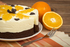 Brownie cake with cream and oranges on the wooden background. Brownie cake with cream and oranges on the brown wooden background Stock Images