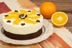 Brownie cake with cream and oranges on the wooden background. Brownie cake with cream and oranges on the brown wooden background Royalty Free Stock Photo