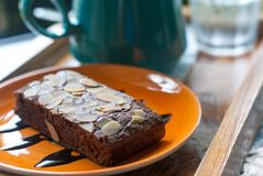 Brownie cake with sliced nut on orange ceramic plate placed in front of coffee mug stock photos