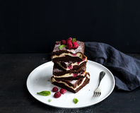Brownie-cheesecake tower with raspberries on white Stock Photos