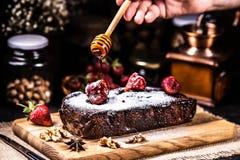 Brownie in chocoladestroop met aardbeien Gietende honing royalty-vrije stock fotografie