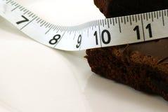 Brownie con la cinta de medición Imagenes de archivo