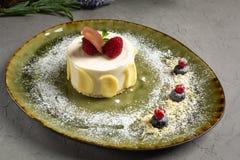Brownie de la avellana con los p?talos del chocolate y el helado en una placa verde foto de archivo libre de regalías