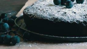 Brownie del dolce di cioccolato coperto generoso di zucchero in polvere che si trova alla moda accanto alle bacche blu video d archivio