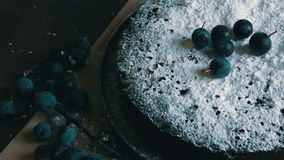 Brownie del dolce di cioccolato coperto generoso di zucchero in polvere che si trova alla moda accanto alle bacche blu archivi video