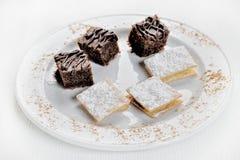 Brownie deliziosi e Alfajores del cioccolato Su una priorità bassa bianca fotografia stock