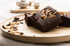 Brownie in dish. Brownies with almond in wood dish on table Royalty Free Stock Photos