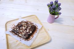 Brownie on dish wood. With  Purple Little Flower in Pot Royalty Free Stock Photo