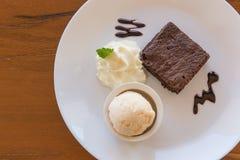 Brownie do chocolate com gelado de baunilha, creme de chicoteamento servido Fotografia de Stock Royalty Free