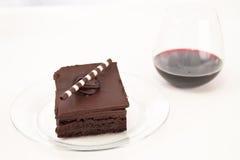Brownie do chocolate e fundo do vinho Imagens de Stock