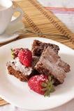 A brownie e a morango deliciosas do chocolate com cacau ordenham Imagens de Stock Royalty Free