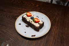 Brownie garnished with whipped cream, strawberries and blueberries in a plate on a dark wooden background royalty free stock images