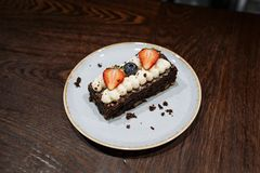 Brownie garnished with whipped cream, strawberries and blueberries in a plate on a dark wooden background royalty free stock photo
