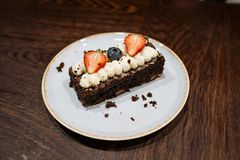 Brownie garnished with whipped cream, strawberries and blueberries in a plate on a dark wooden background stock photography