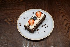Brownie garnished with whipped cream, strawberries and blueberries in a plate on a dark wooden background royalty free stock photos