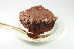 Brownie glassato cioccolato Gooey con la forcella dorata. Immagine Stock