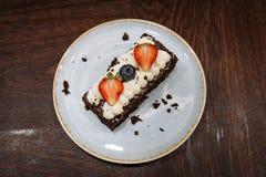 Brownie guarnito con crema, le fragole ed i mirtilli montati in un piatto su un fondo di legno scuro fotografia stock
