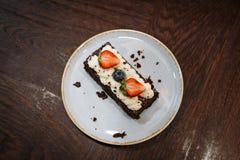 Brownie guarnito con crema, le fragole ed i mirtilli montati in un piatto su un fondo di legno scuro fotografia stock libera da diritti