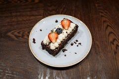 Brownie guarnito con crema, le fragole ed i mirtilli montati in un piatto su un fondo di legno scuro fotografie stock libere da diritti