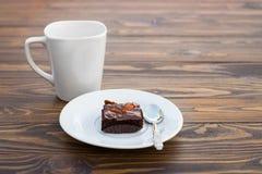 Brownie hecho en casa del chocolate con la almendra y una taza blanca de la taza Imagen de archivo