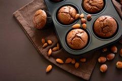 Brownie hechos en casa de los molletes del chocolate con canela, almendras y avellanas en fondo del papel marrón Fotografía de archivo libre de regalías
