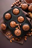 Brownie hechos en casa de los molletes del chocolate con canela, almendras y avellanas en fondo del papel marrón Imágenes de archivo libres de regalías